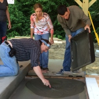 John Baymore leveling the cement pad with Eric Maglio and Belinda Bodnar